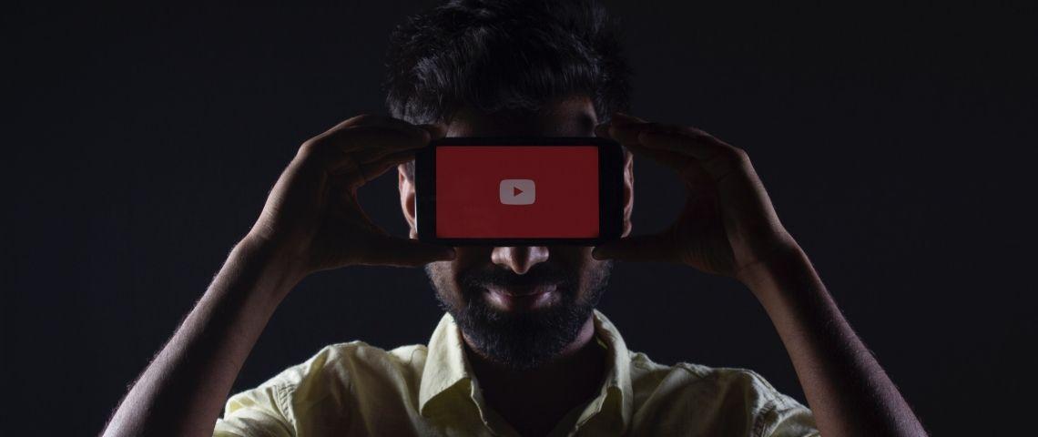 Un homme dissimulé derrière un smartphone sur YouTube