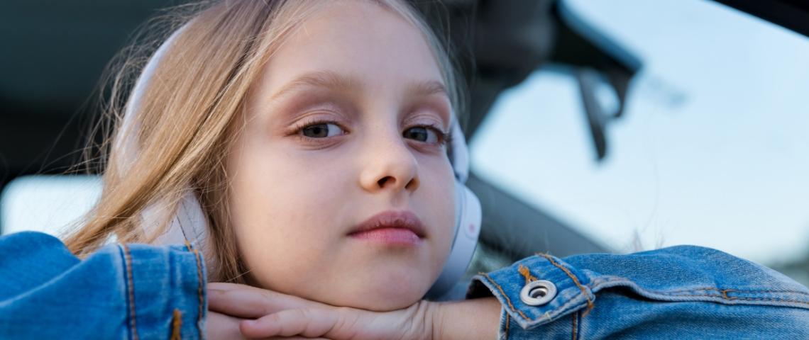 Une petite fille avec un casque audio sur les oreilles