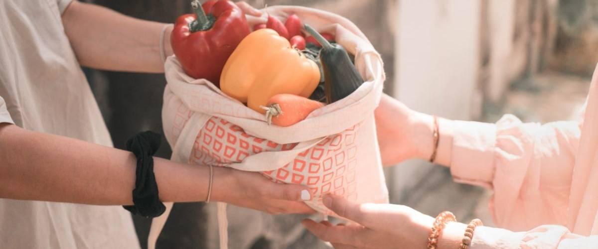 Deux personnes s'échangent un sac de fruits et de légumes
