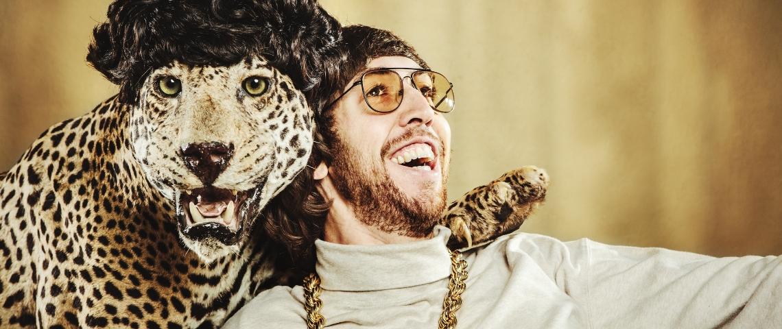 un homme pose avec un léopard empaillé