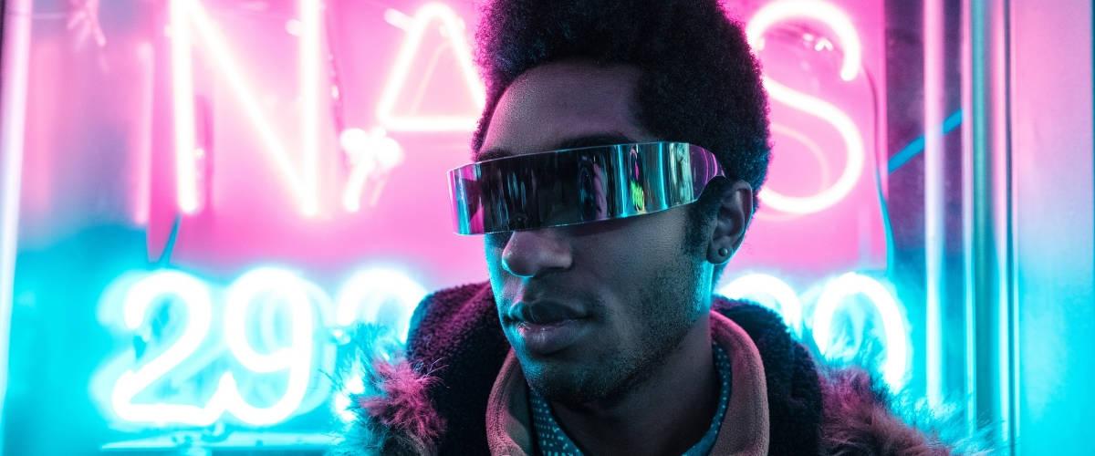 Un homme noir avec des lunettes devant des néons