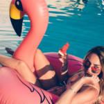 Une femme dans une piscine avec un bouée en forme de flamant rose