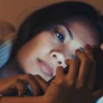 une jeune fille asiatique regarde un smartphone allongée dan un lit