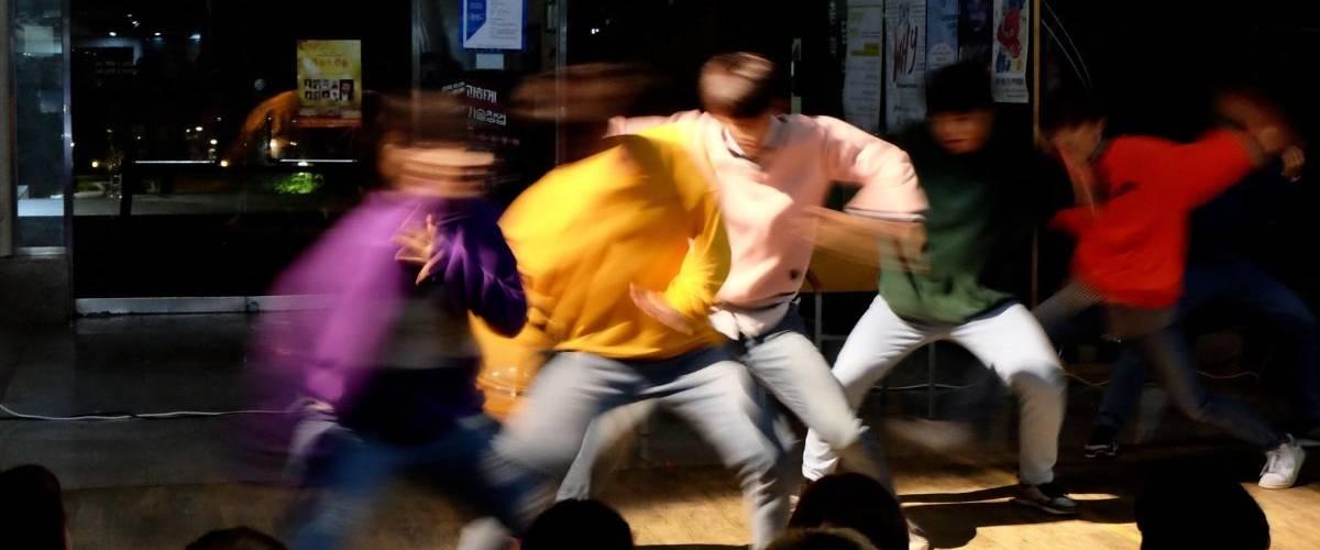 Un groupe d'hommes danse dans une rue coréenne