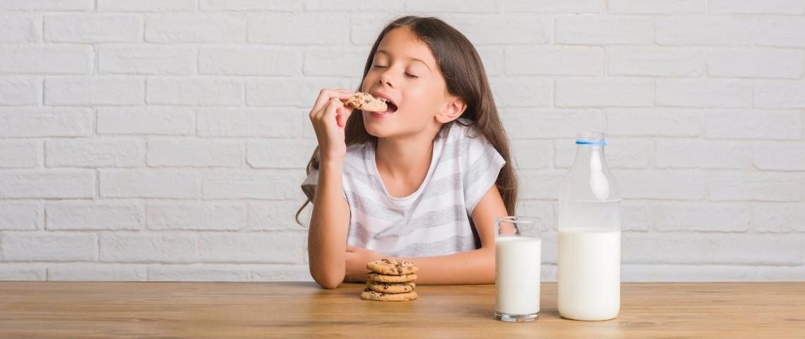 Un jeune enfant aux cheveux longs en train de manger un cookie trempé dans un verre de lait