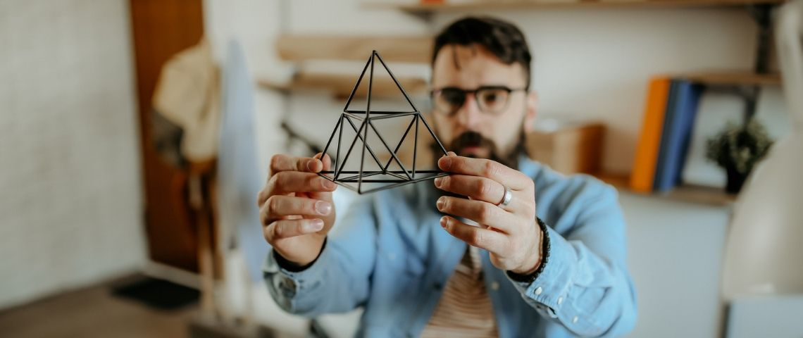 Un homme designer tient un prisme dans sa main
