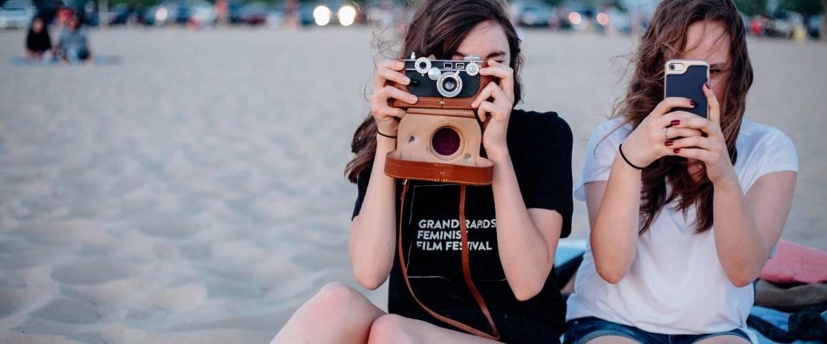 Deux jeunes adolescentes prennent des photos à la plage sur leur téléphone et un appareille photo