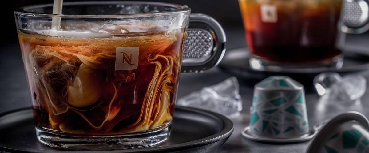 Sur une table se trouve une tasse de café Nespresso dans laquelle on verse un nuage de lait. A gauche, une capsule Nespresso