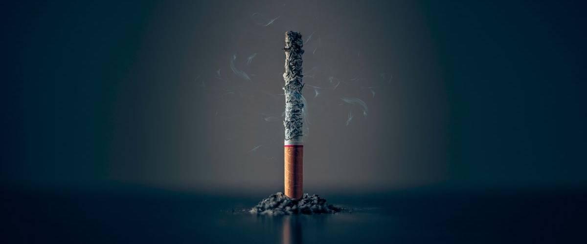 une cigarette consumée, sur un fond noir
