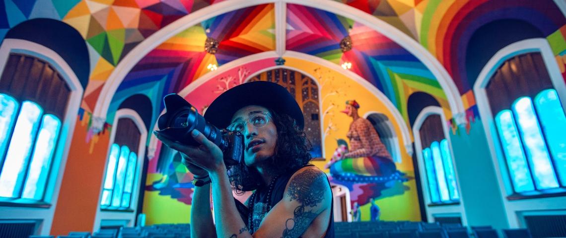 un homme tatoué prend une photo dans une église colorée