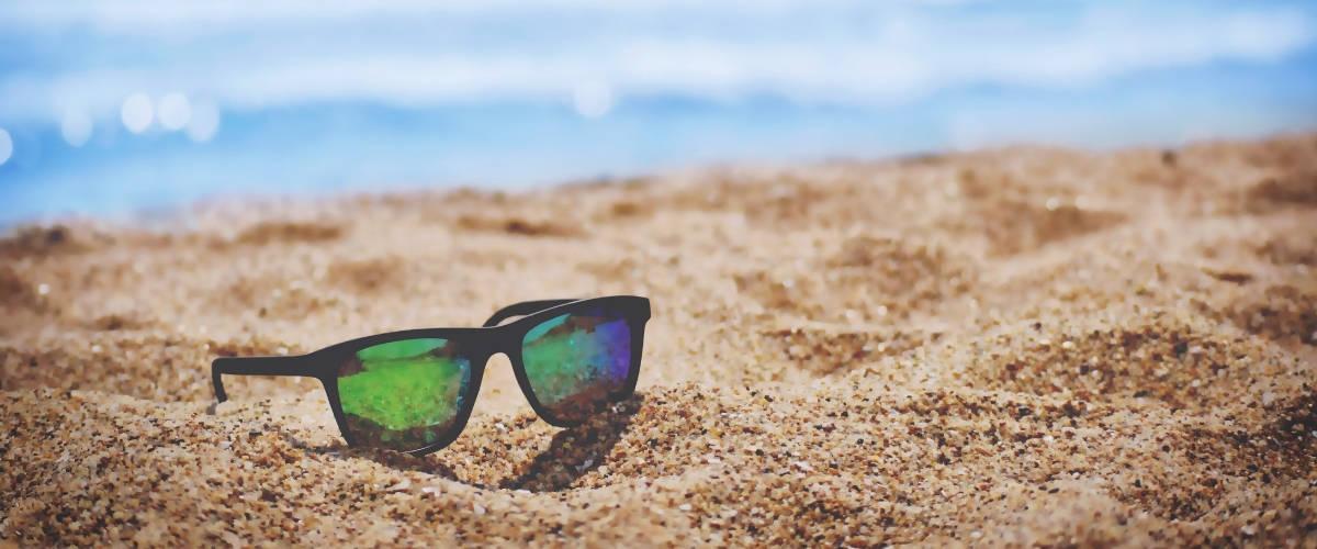 Une paire de lunette de soleil sur le sable