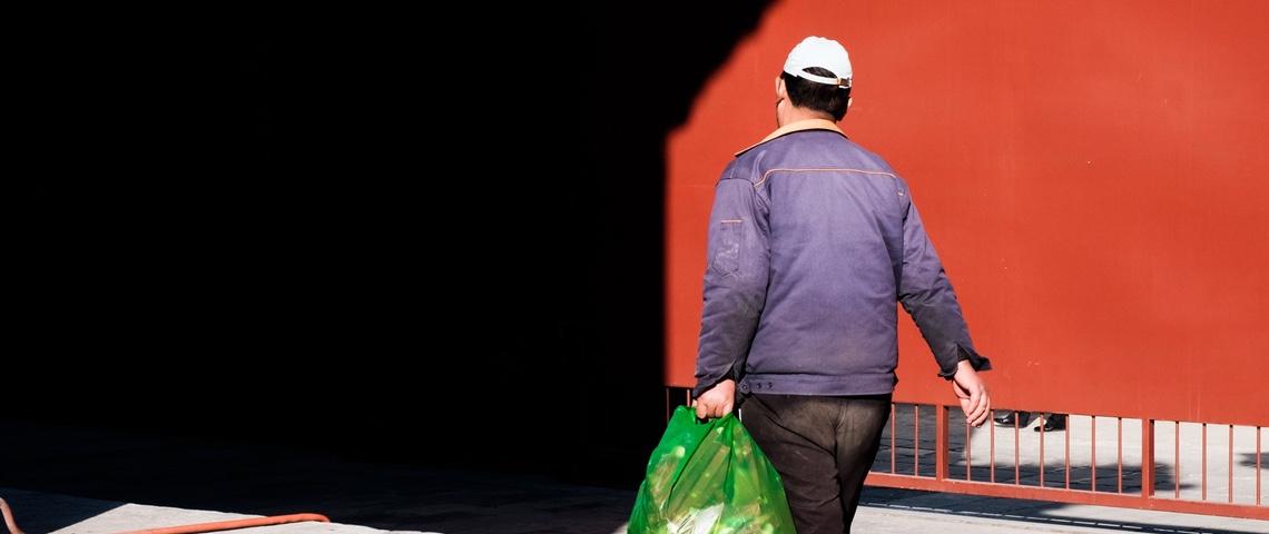 Un homme asiatique de dos tient un sac poubelle
