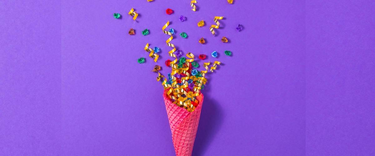 Un cornet rose avec des confettis