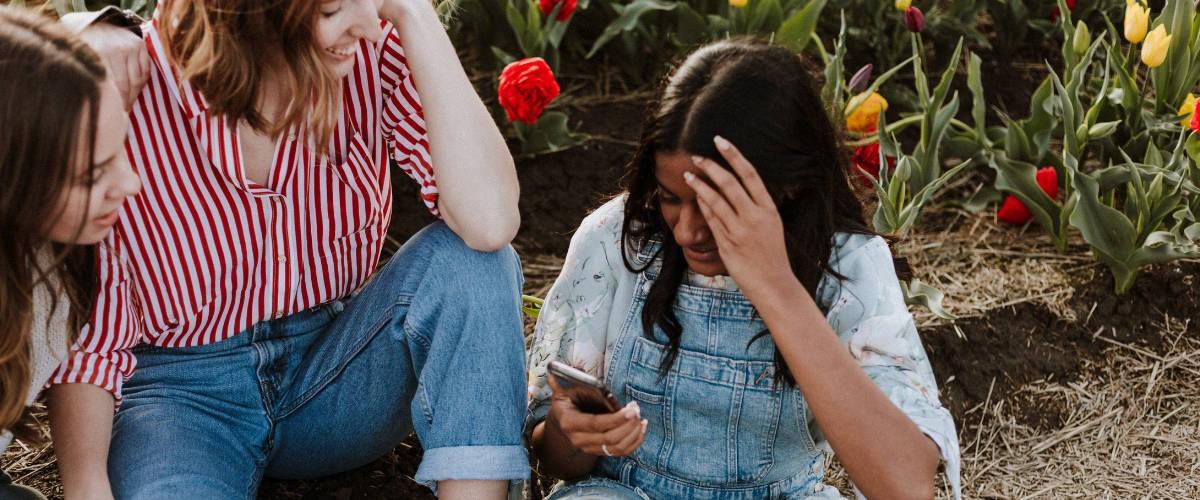 Des femmes assises par terre avec un smartphone