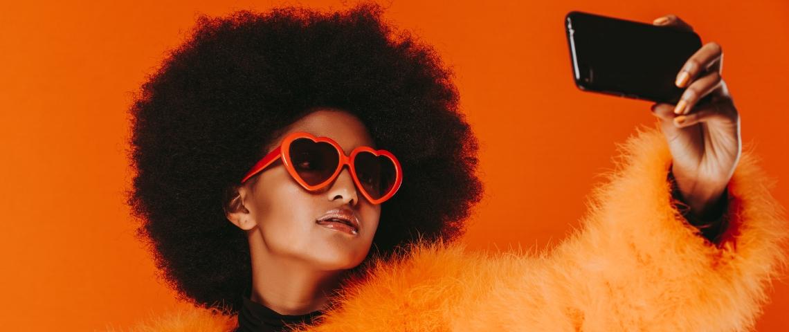 une jeunes fille à la coupe afro se prend en photo
