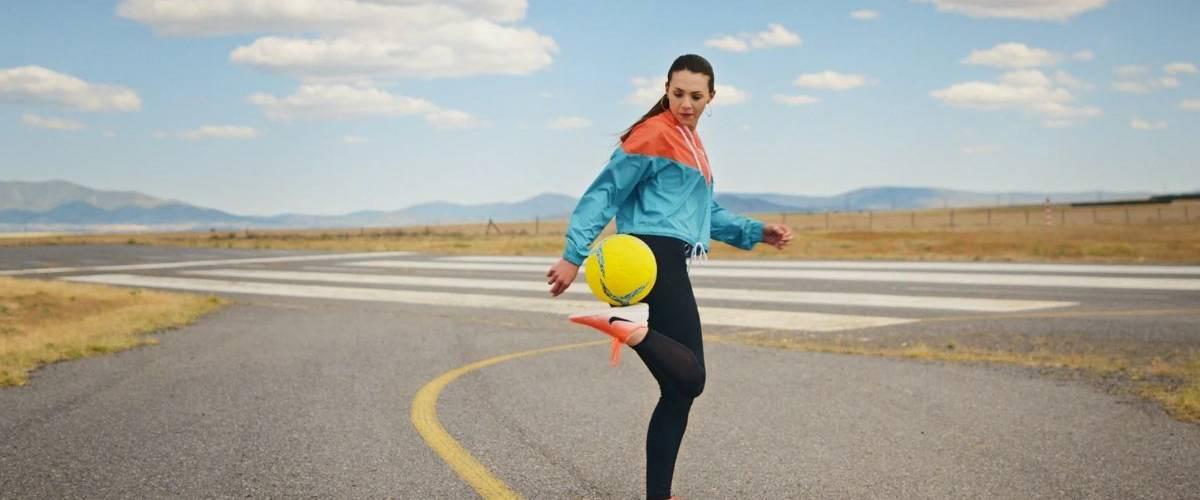 Une joueuse de football jongle avec son ballon sur une route désertique
