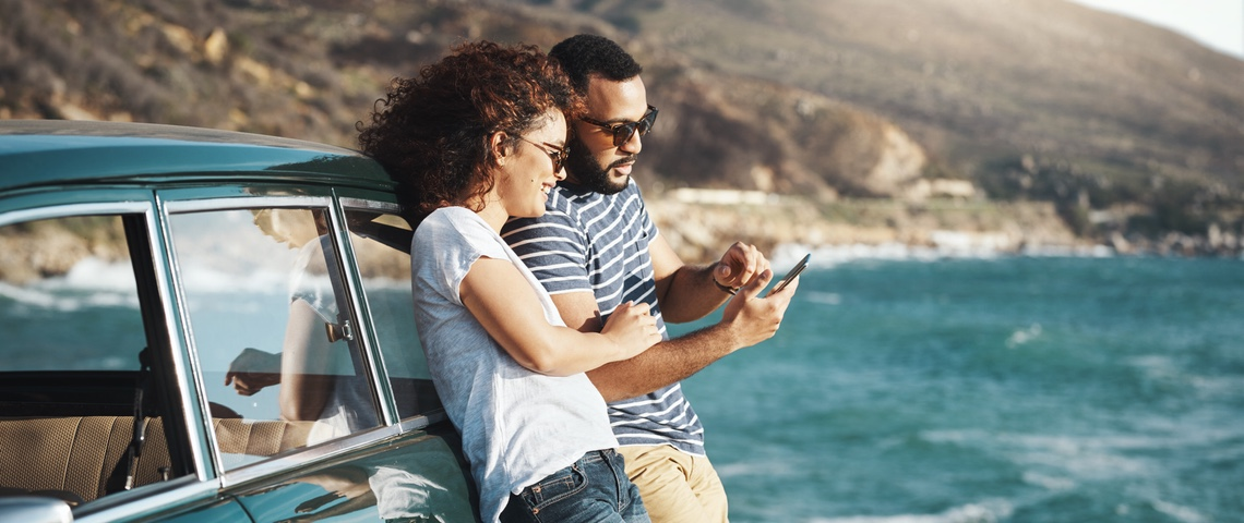 Couple adossé contre voiture vintage à la mer, regardent un smartphone