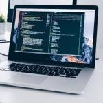 Un ordinateur sur un bureau affiche des codes HTML