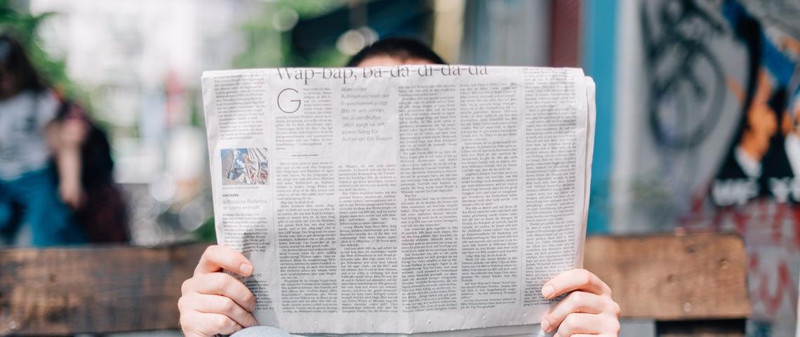 Personne lisant un journal sur un banc.