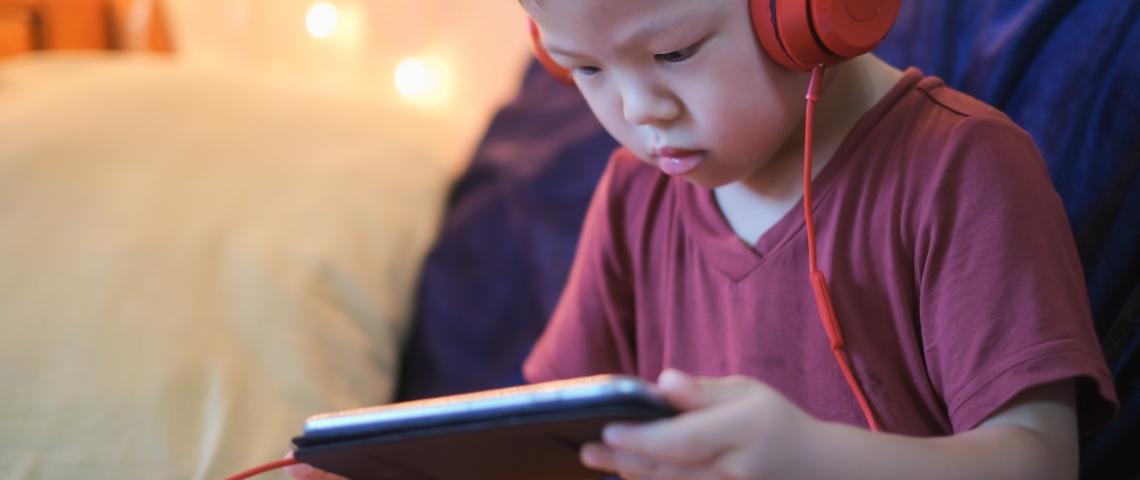 un petit garçon avec des gros écouteurs regarde un écran