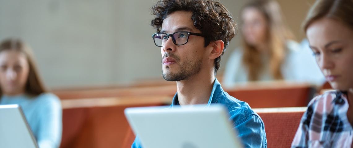 Étudiant derrière un ordinateur en salle de classe