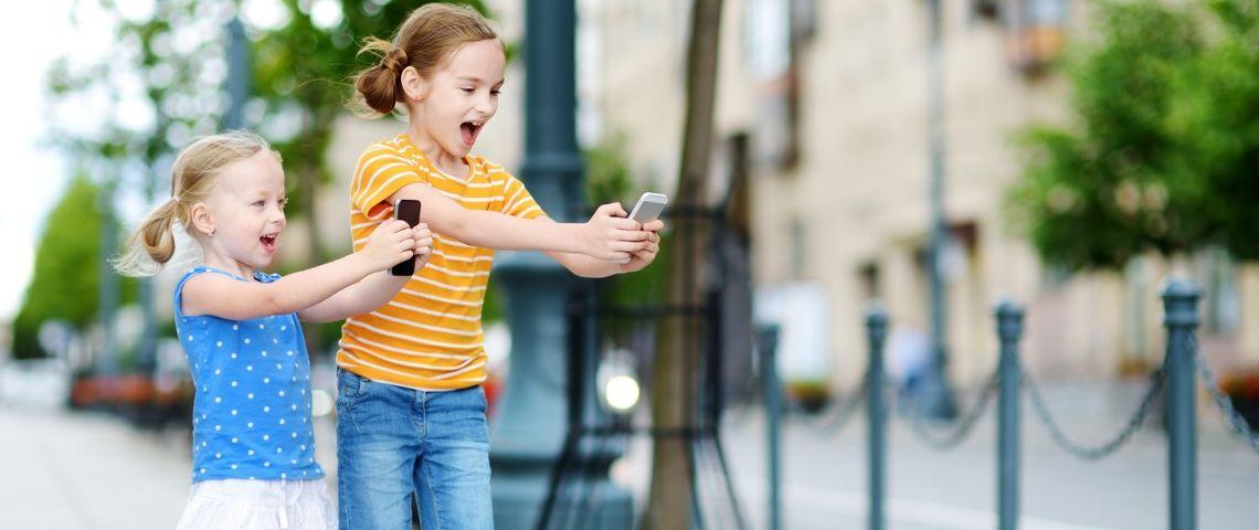 Deux petites filles jouent avec un smartphone