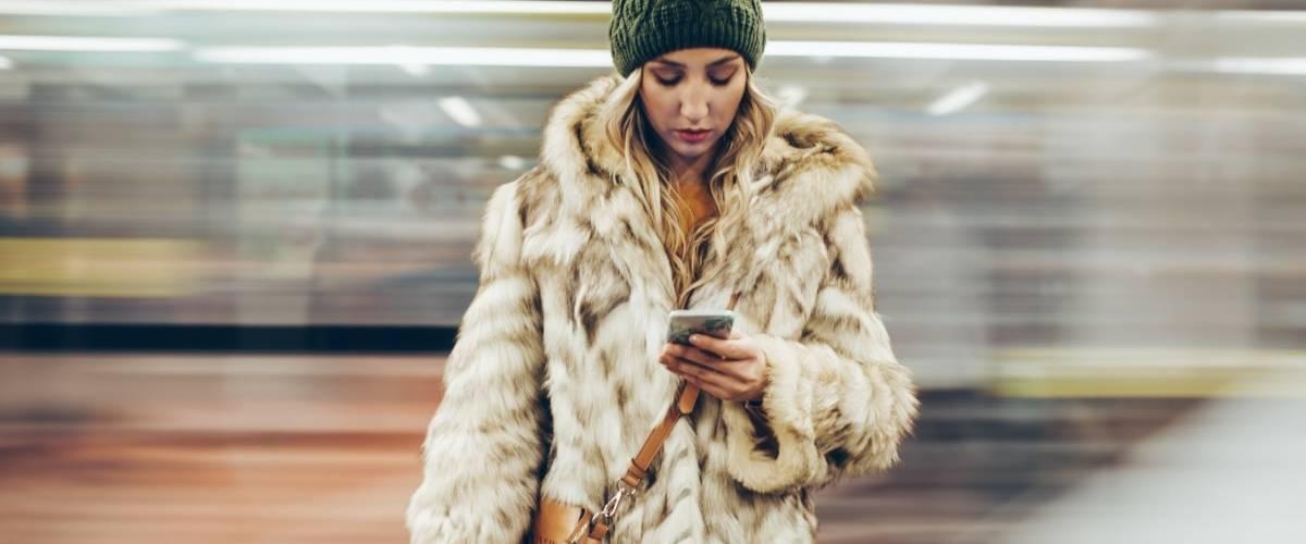 Une femme avec un manteau en fourrure sur le quai d'un métro