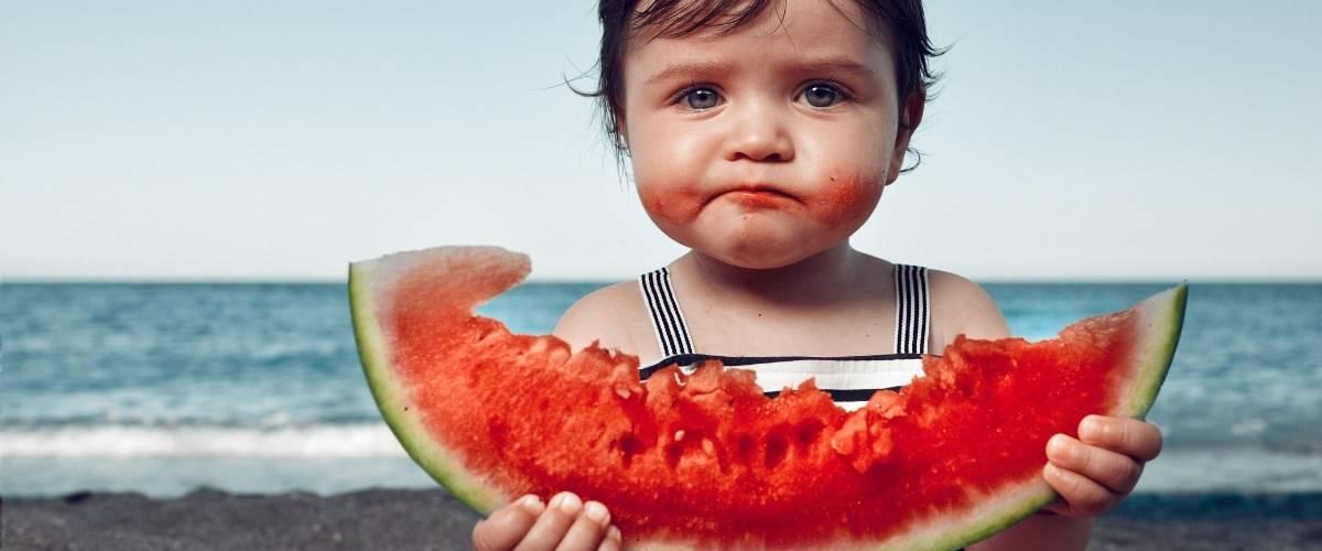 Une petite fille à la plage en train de manger une pastèque