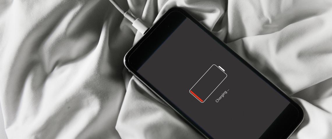 Smartphone en train de charger sur un lit