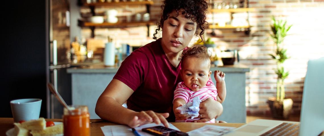 Une femme travaillant sur son ordinateur avec un enfant dans les bras