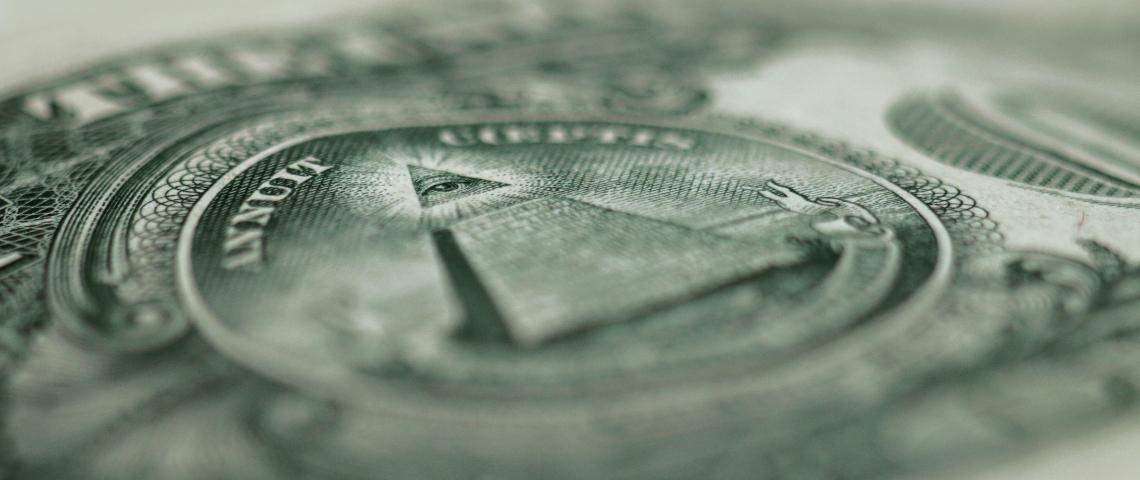 Un gros plan sur un billet en dollars avec la pyramide et la devise in god we trust