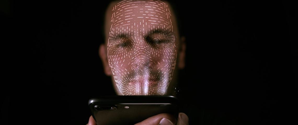 Homme se faisant identifier grâce à reconnaissance faciale de son smartphone.