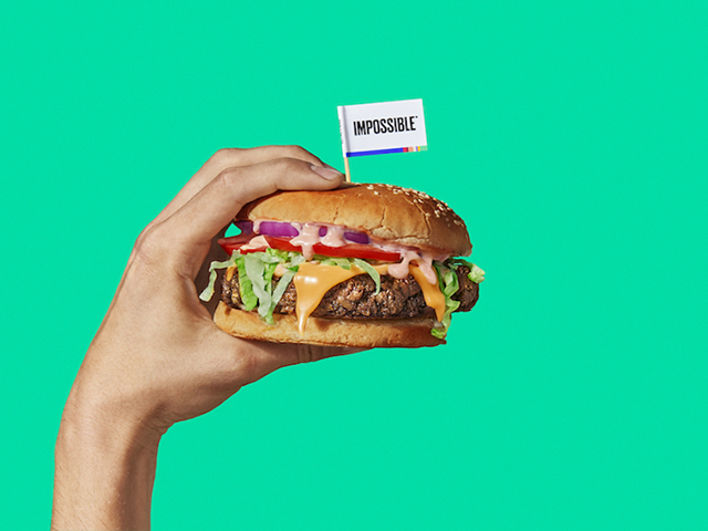 Une main qui tient un hamburger sur un fond vert