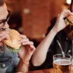 Un homme et une femme qui mangent des burgers