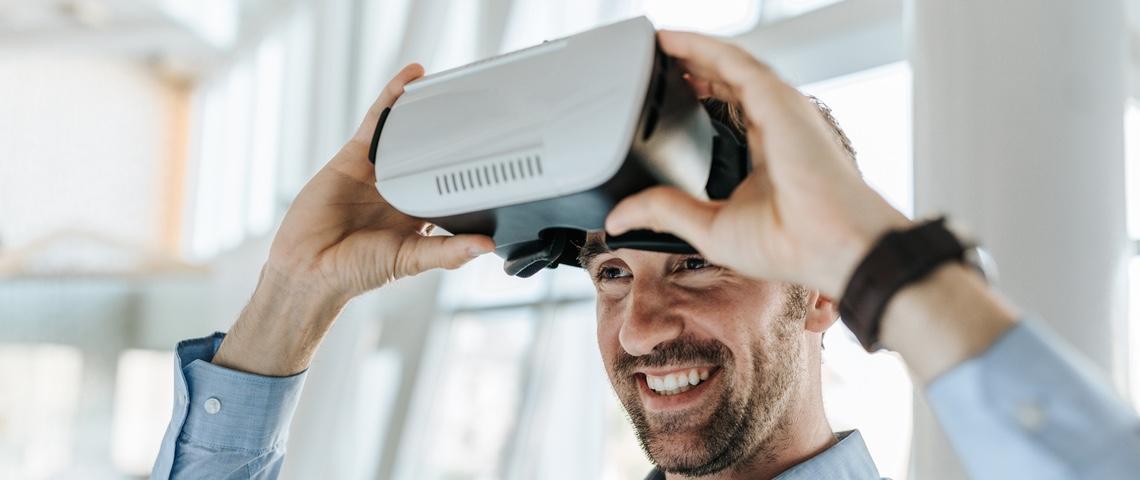 Un homme souriant met un casque de réalité virtuelle.