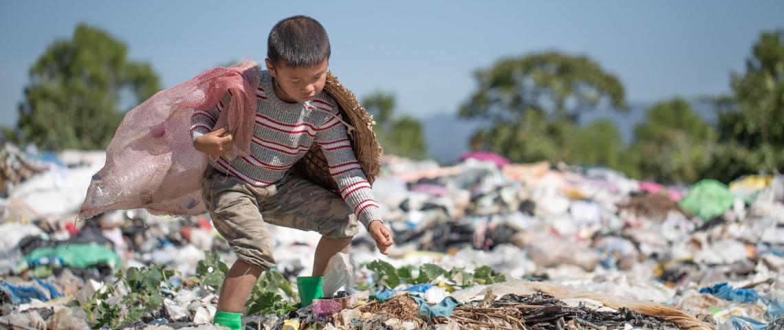 Un petit garçon en train de ramasser des déchets dans une décharge plastique à ciel ouvert