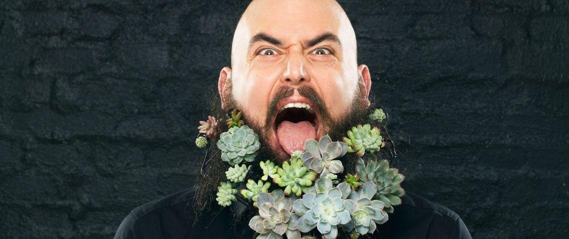 Un homme barbu envahi de plantes vertes