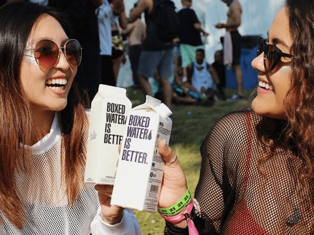 Deux jeunes femmes qui boivent de l'eau à un festival