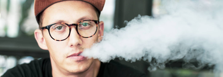 jeune homme fumant une ecigarette en faisant de la fumée