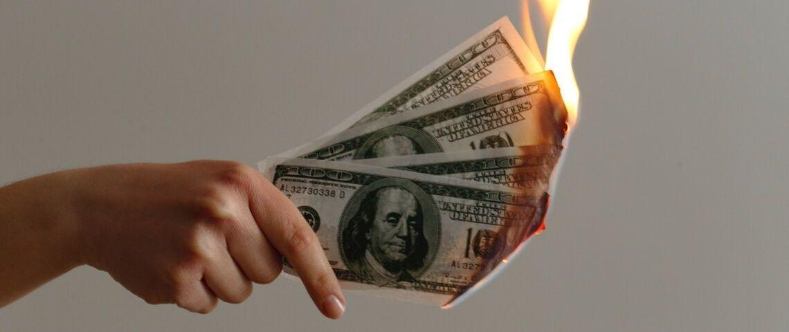 Une main qui tient des billets de dollars en feu