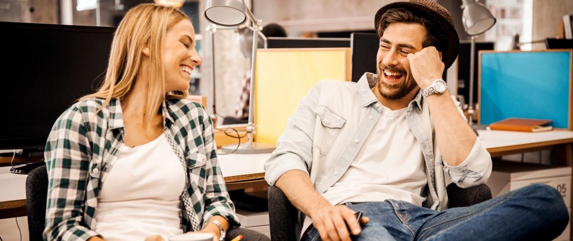 Un homme et une femme en train de rire au bureau