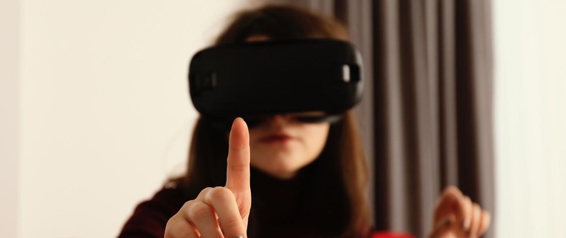 Femme portant un casque de réalité virtuelle essaye de toucher un objet