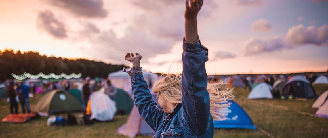Jeune femme danse et lève les bras pendant un festival de musique.