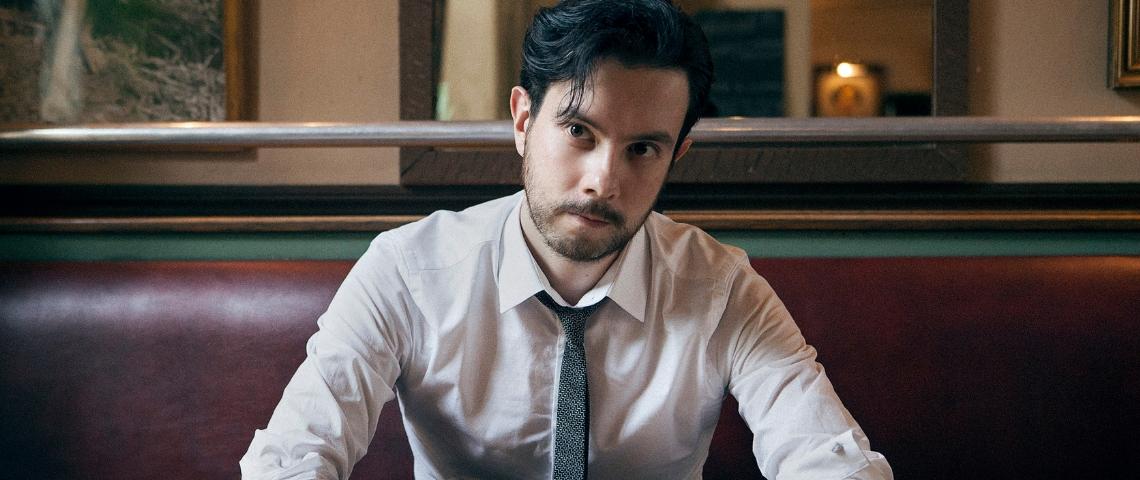 un jeune homme en cravate assis dans un bistro