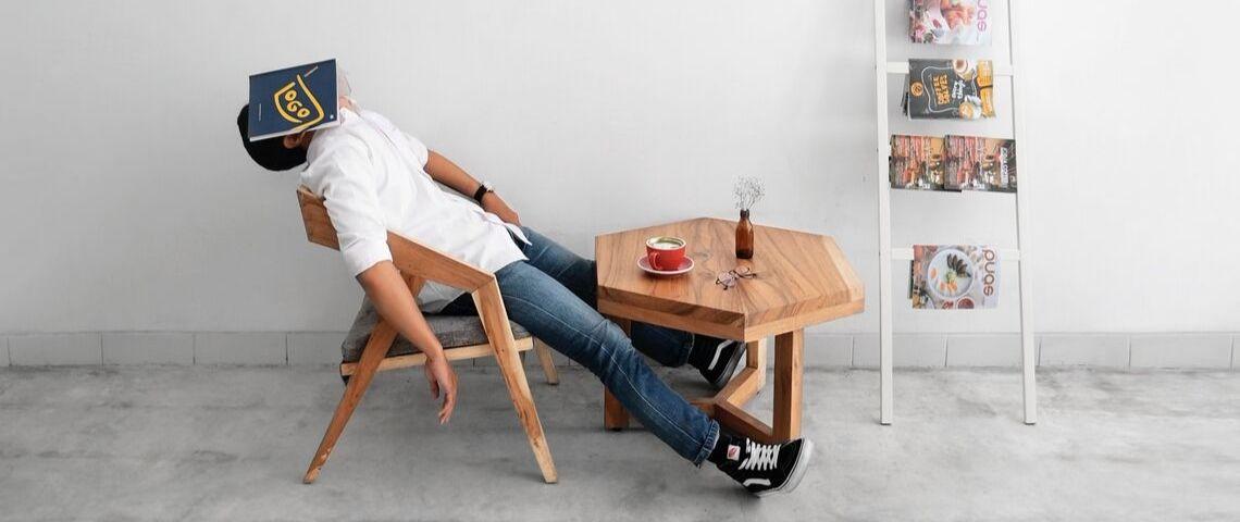 Un homme fatigué se repose avec un livre posé sur son visage