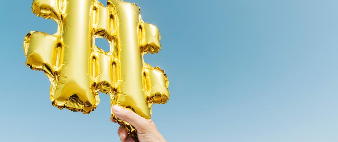 une main tient un ballon doré en forme de dièse