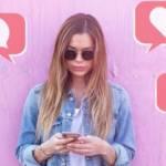 Une jeune femme en veste en jean posant devant un fond rose et utilisant son téléphone portable