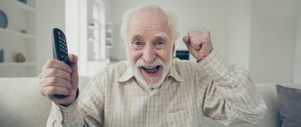 Un homme âgé sourit et tient une télécommande sur son canapé