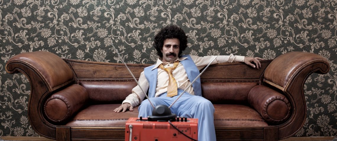 Un homme déprimé sur son canapé, dans une décoration très seventies.
