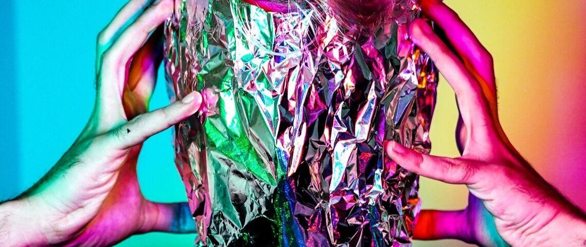 Un humain se tient la tête enroulée dans de l'aluminium